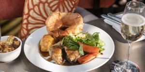 Sunday roast with a giant yorkshire pudding and a glass of white wine.