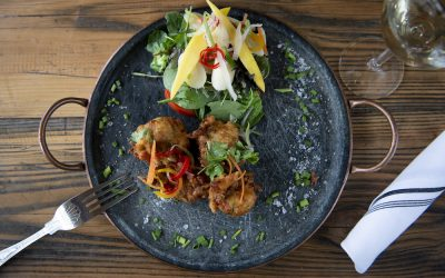 Pakoras served with an aromatic salad, fresh herbs and a glass of white wine. Displayed on a black rustic tray.