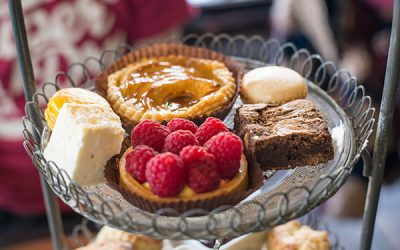 Afternoon tea patisserie tier including a raspberry tart, brownie, apple pie and macarons
