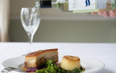 Roast pork with fondant potato and kale. Served with gravy and a glass of wine bering poured in the background.