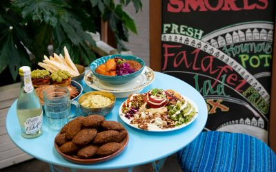 A dish of falafal with plates of salad and homous on a blue table,