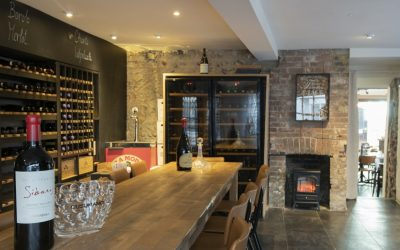 A long wooden banquet table is in a stone room with wine racks and fridges along one wall.