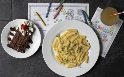 A plate of pasta and a portion of chocolate cake with sauce and cream. Served alongside kids colouring pages and crayons.