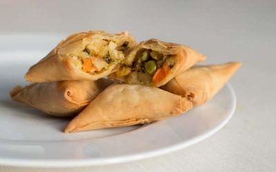 Samosas served on white plate and table