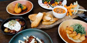 A selection of starters served on colourful plates and a wooden board.
