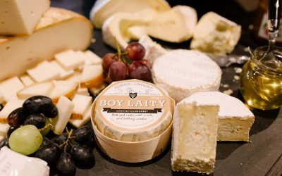 A cheese board packed full of different cheeses and juicy grapes.