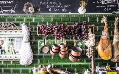 Dried chillies, cured meats and copper pots and pans hanging on a green tiled wall