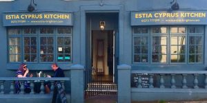 Photograph of the front street exterior and alfresco dining of Estia restaurant with dark blue paintwork, windows and gold signage.