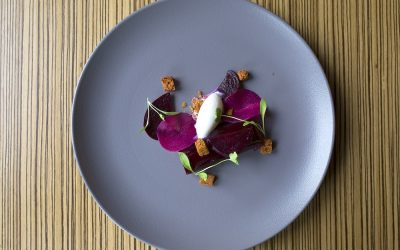 Beetroot Dish garnished with microgreens served on a purple ceramic plate.