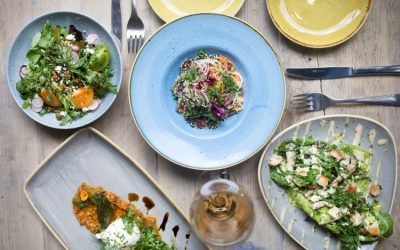 Fresh salads with butternut squash and dressings served in blue and grey ceramic plates