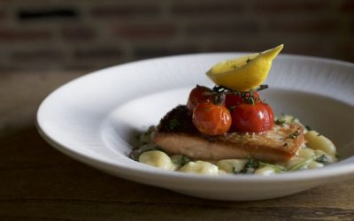 Salmon fillet on a bed of creamy new potatoes with roasted vine cherry tomatoes and lemon. Served in a white dish and photographed against a red brick wall.