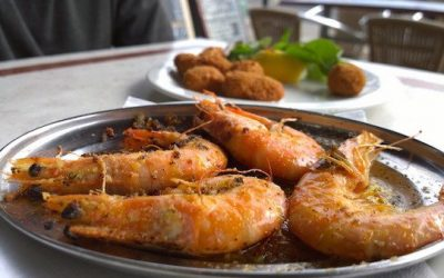 Garlic king prawns served on a plate with a side dish in the background.
