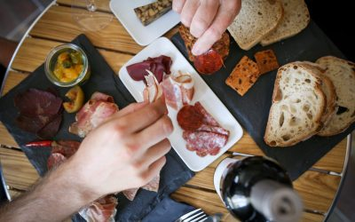 Sharing charcuterie platter served on slates with slices of bread and a bottle of wine.