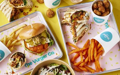A spread of vegan fast food, burgers, wraps, chips and salad bowls.