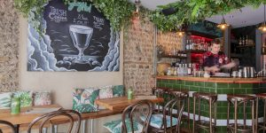 Inside Gungho bar, a blackboard advertising a seasonal cocktail, floral patterned 80s cushions, hanging plants and a green tile bar