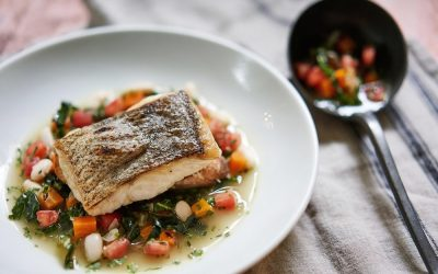 Pan-fried hake on a bed of chopped tomatoes, herbs and sauce. Served on a white plate with a spoon.