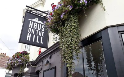 Exterior of Haus on the Hill with hanging basket of flowers.