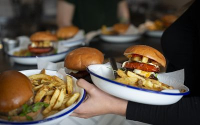 Burgers and fries in brioche buns served on enamel dishes