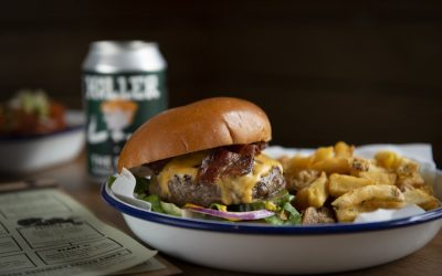 A cheese burger with bacon served in a brioche bun with skinny fries in a blue and white enamel dish.