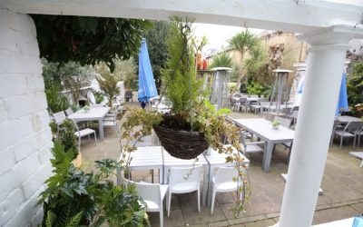 A beer garden with white furnishings and lots of plants.