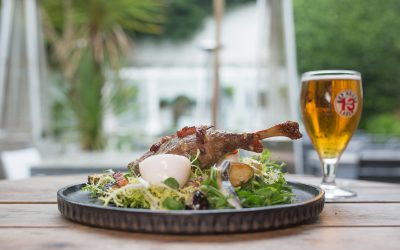 A plate of chicken and egg salad with a pint of beer on a wooden table in a pub garden.