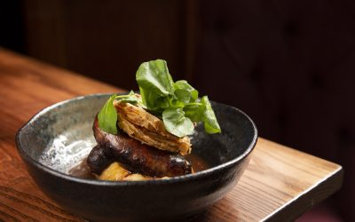 A rustic black bowl with sausages and mashed potato topped with fresh watercress.
