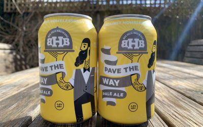 Yellow and grey artwork on two craft ale beer cans sat on a wooden table in the sun