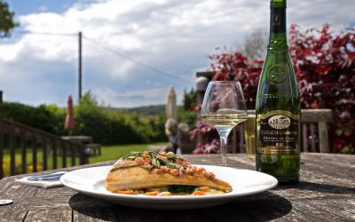 A plate of fish with samphire and a bottle of white wine. Served outside in a garden on a sunny day with a bootle of wine.