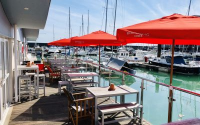 Water side decking and seating at The Watershed with red parasols for shade and views over the yachts