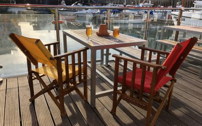 Two canvas chairs at a table on the Brighton marina waterfront with two beers on the table.