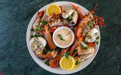 A large seafood platter with lobster, crab and scallops. Served on a large round tray with a seafood dip and fresh lemon.