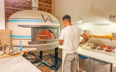 Chef cooking pizza at Woodbox Pizzeria in a pizza oven.