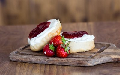 Cream tea scone with clotted cream and strawberry jam presented on a wooden chopping board with fresh strawberries.
