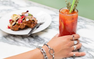 hand with rings on each finger holding bloody mary cocktail