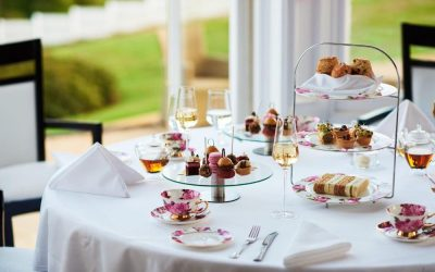 High tea served on a table dressed with a crisp white table cloth. Serving a variety of French patisseries, cake and champagne.