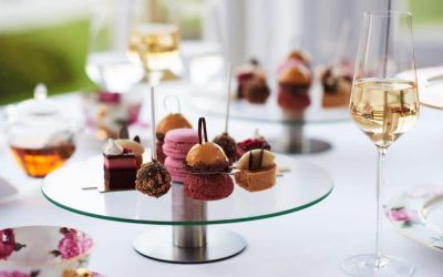 Pretty French patisserie sweets served on a glass cakes stand with glasses of champagne.