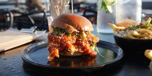 K-Pop burger on the sunny terrace with a carafe of water
