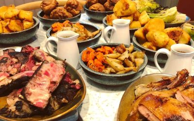 A roast dinner feast including bowls of roast potatoes, carrots, parsnips, jugs of gravy and sliced meats.