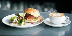 Brunch burger with bacon and fresh salad, served with a cappuccino.