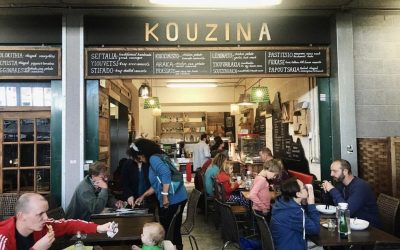 Hustle and bustle outside dining at Kouzina at the open market with people dining and the Kouzina sign displayed against the black paintwork.