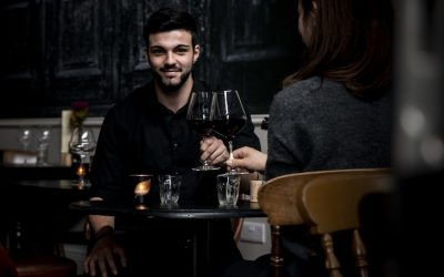 Two people with a glass of red wine at the table