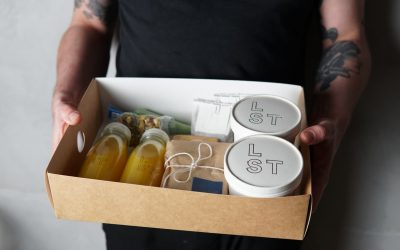 A cardboard box being held including bottles of fresh orange juice and containers of brunch food.