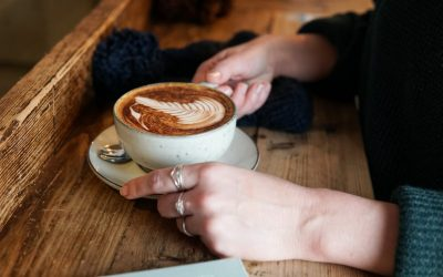 A woman's hands holding a cup of coffee on a wooden bench