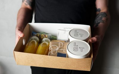 Brunch box displaying fresh orange juice and containers of food.