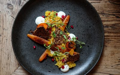 A black plate with miso carrots and pomegranate seeds