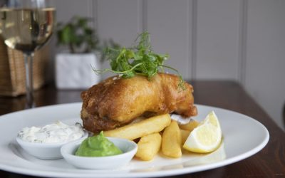 A plate of battered fish laid on top of chunky chip with tartare sauce and mushy peas