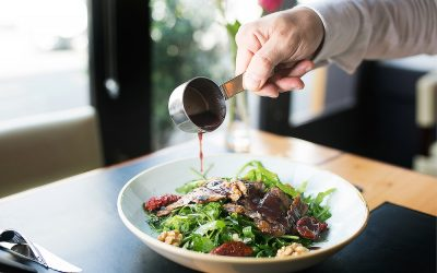 Steak salad with a sauce being poured over. Photographed next to a window with natural light.