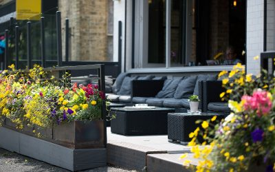 Alfresco seating at Libation with cushioned black sofas and summer flowers