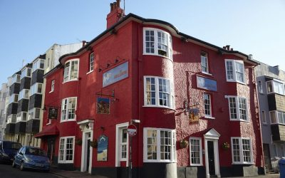 Exterior shot of the red painted Lion and Lobster pub on a sunny day with a clear blue sky.
