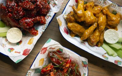Trays of chicken wings cooked in different sticky sauces with a side of celery and creamy dip